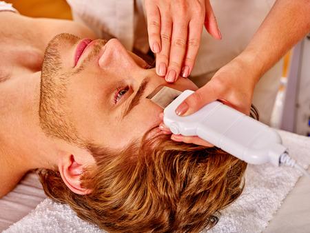sound therapist: Man receiving electric facial ultrusound peeling at beauty salon.