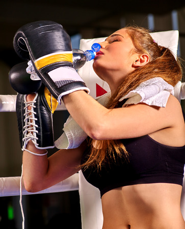 showgirl: Girl boxer wearing gloves drinking bottle water sitting in corner of boxing ring.