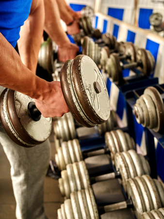 sports equipment: Close up og man hand working his arms with dumbbells at gym. He lifting dumbbells. Stock Photo