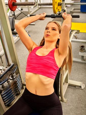 salud y deporte: La mujer en el deporte desgaste rojo trabajar los brazos y el pecho en el gimnasio. Bíceps curl máquina.