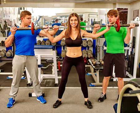 salud y deporte: Mujer y dos hombres que trabajan los brazos y el pecho en el gimnasio. Ella Barbell de elevación.