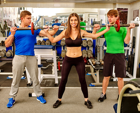exercise equipment: Woman and two men working his arms and chest at gym. She lifting barbell.