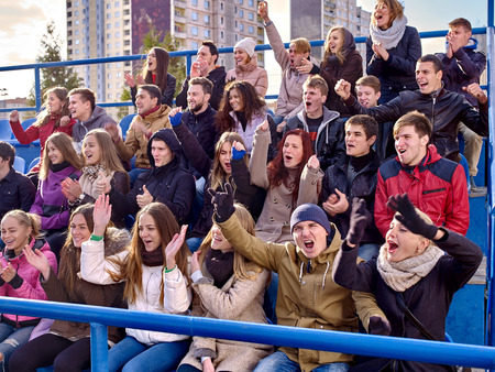 grandstand: Sport fans clapping and singing on tribunes. Group emotion people. Stock Photo