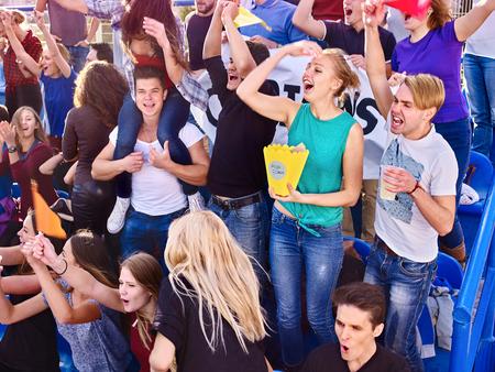 personas comiendo: Los fanáticos del deporte comiendo palomitas de maíz y cantando en tribunas. emoción grupo de personas.