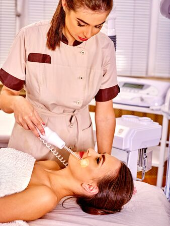 medical treatment: Young woman receiving electric luminous darsonval facial  procedure at beauty salon.