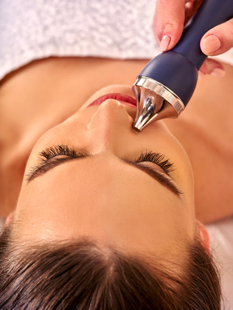 sound therapist: Woman receiving electric ultrusound facial massage at beauty salon. Close up.