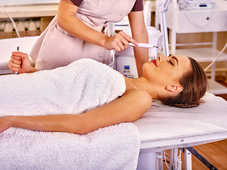 sound therapist: Lying woman receiving electric facial eyes massage on microdermabrasion equipment at cosmetic salon. Stock Photo