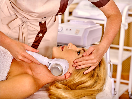 electrophoresis: Young blonde woman receiving electric facial massage on microdermabrasion equipment at hardware cosmetology salon.