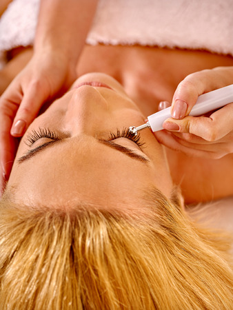 rf: Close up of  woman close up  receiving electric facial eyes massage on microdermabrasion equipment at beauty salon. Stock Photo