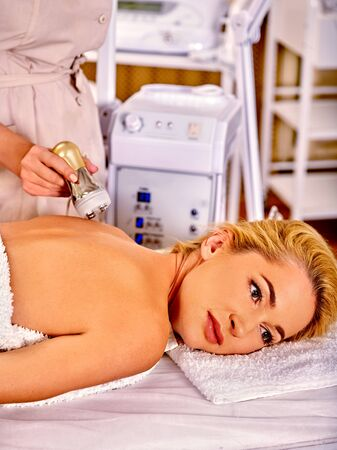 hight tech: Woman receiving electroporation back therapy at beauty  hardware cosmetology salon.