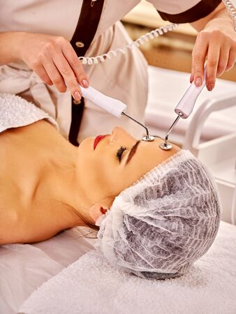 photon: Head of  woman receiving electric facial eyes massage on microdermabrasion equipment at beauty salon. Indoor.