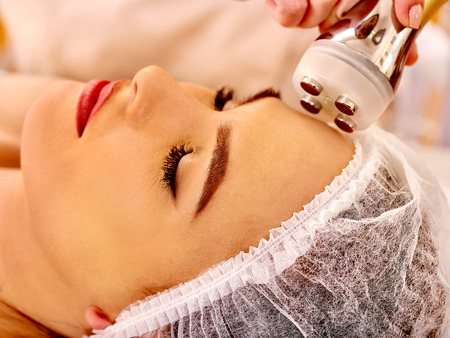 Close up of head woman receiving electroporation  facial therapy at beauty salon.