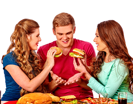 two women and one man: Group people eating hamburgers .Girls fed burger man. Fast food concept with two women and one man . Isolated.