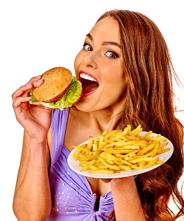 HAMBURGUESA: Muchacha que come la hamburguesa y patatas fritas. Concepto de la comida rápida.