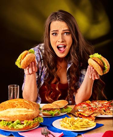 woman eat: Girl eat fastfood big hamburger and pizza .