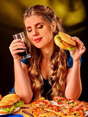hamburger: Girl eating  hamburger with pizza and drink cola. Fastfood concept. Stock Photo