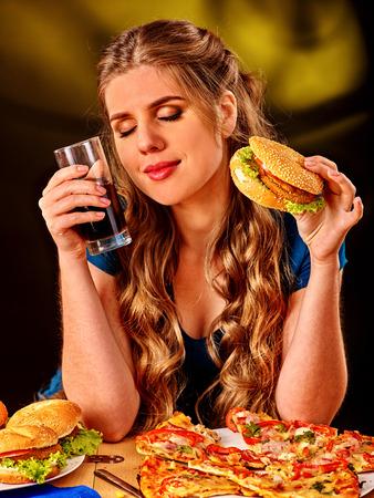 HAMBURGUESA: Muchacha que come la hamburguesa con pizza y refresco de cola. Concepto de la comida rápida. Foto de archivo