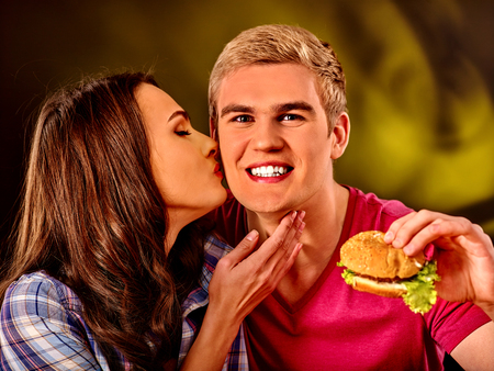 fastfood: Young couple male and woman eating hamburgers . Fastfood concept. Woman kissing man. Kho ảnh