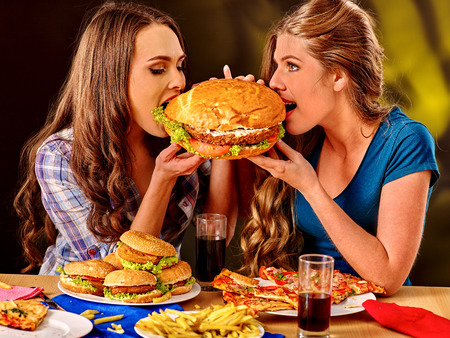 fastfood: Girls bite burger with two sides. Fastfood concept.