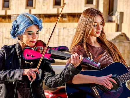 solitariness: Music street performers two girls violinist with blue hair playing  aganist city outdoor. Stock Photo