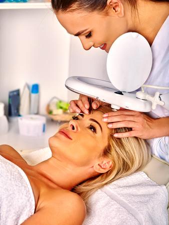 Femme d'âge moyen se situant dans un salon de spa avec correction des sourcils de la lampe cosmétique. Banque d'images