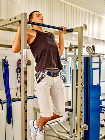 gripping bars: Man pulling on the bar in gym. Pull ups.