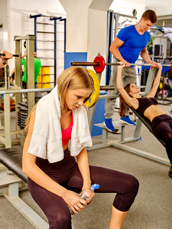 sport woman: Exhausted young woman with towel working his arms and chest at gym. She relax near barbell.