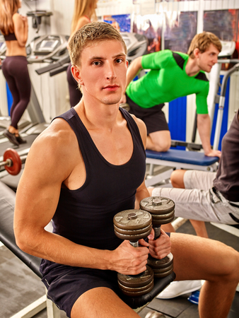 woman relaxing: Group of people working with  dumbbells his body at gym. Portrait of handsome man. Stock Photo