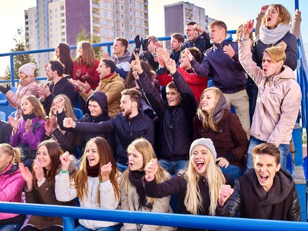 grandstand: Sport fans hands up clapping and singing on tribunes. Group people. Stock Photo