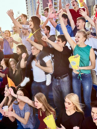 man sit: Sport fans hands up eating popcorn  and singing on tribunes. Group people. Stock Photo