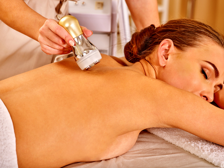 depressor: Lying woman with close eyes receiving electroporation back therapy at beauty salon.
