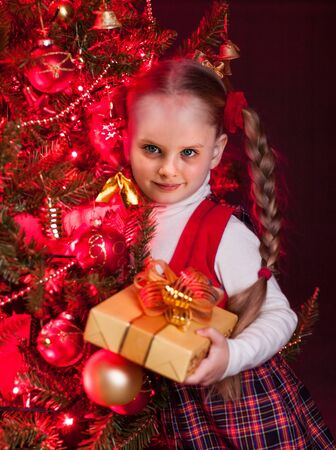 open present: Child little girl holding gift box near Christmas tree with glowing  lights.