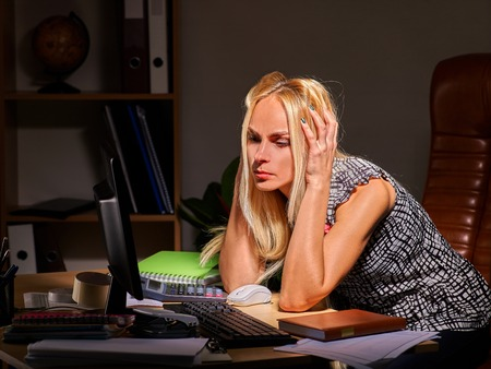 work addicted: Woman at computer late at night take head. Social network addiction. Stock Photo