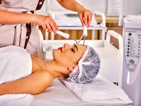 cosmetologies: Close up of  woman wearing hat  receiving electric facial eyes massage on microdermabrasion equipment at beauty salon.