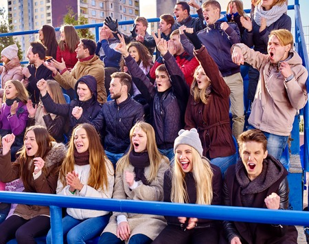 grandstand: Sport fans clapping and crying on tribunes. Group adult people.