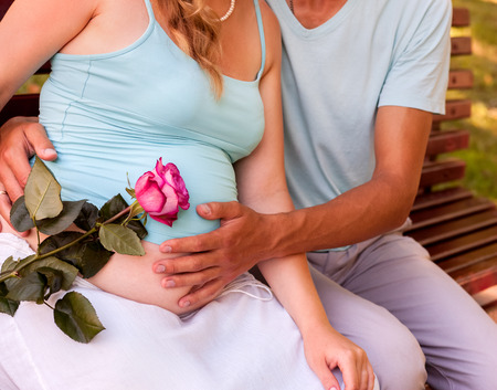 enceinte: Body part of pregnant woman, holding flower with man  outdoor in park. Stock Photo