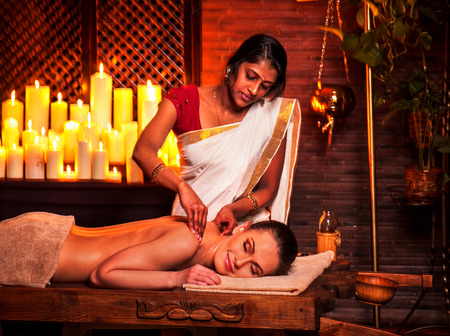 india woman: Young woman having oil Ayurveda spa treatment in India salon. Stock Photo