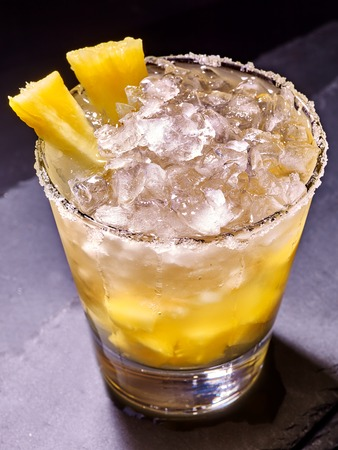 amarillo y negro: Yellow cube ice of cold drink  with  pineapple on dark background. Cocktail card 84.