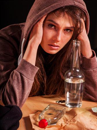 drunk girl: Drunk girl holding bottle of alcohol. Soccial issue alcoholism on dark background. Stock Photo