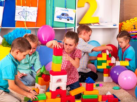 Group children girls and boys game blocks on floor in kindergarten . Top view.