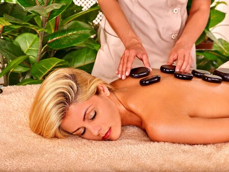 stone therapy: Woman with closed eyes getting relaxing stone therapy massage. Stock Photo