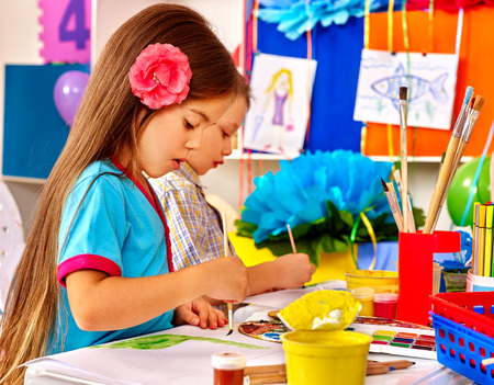 kids club: Little girl and boy with brush painting on table in  kindergarten . Stock Photo