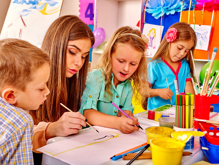 Children with teacher woman learn painting on paper at table in kindergarten . Stock Photo