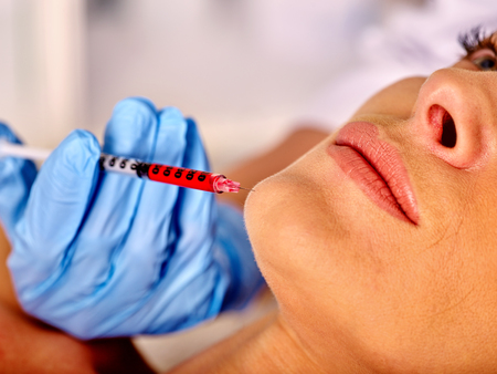 Woman middle-aged giving face botox injections in spa salon .