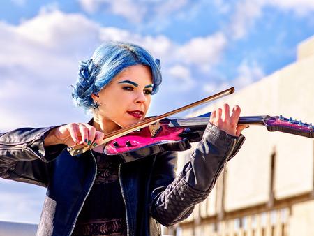 Schöne Musik Straßenkünstler Mädchen Geiger mit dem blauen Haar mit Wolken aganist Himmel spielen im Freien.