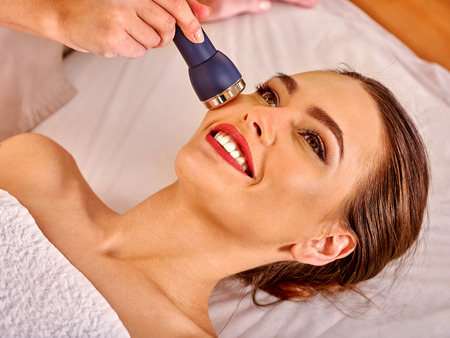 procedures: Portrait of young smiling woman receiving electric ultrusound facial massage at beauty salon.