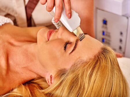 rf: Woman receiving electric facial ultrusound peeling .