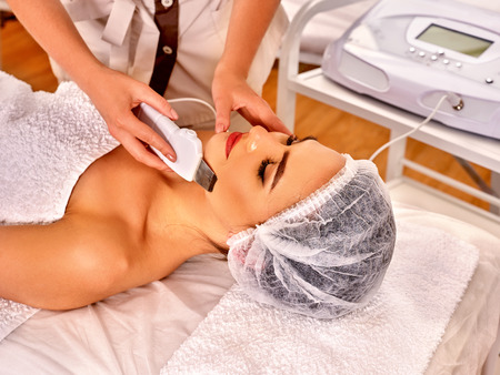 healing with sound: Woman receiving electric facial peeling treadment at beauty salon.