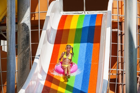 child sport: Female kid on water slide at aquapark. Summer holiday.