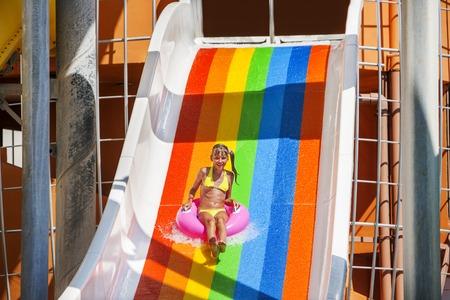 enfant qui joue: kid Femme sur la diapositive de l'eau à aquapark. Vacances d'été.